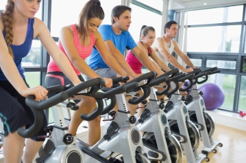 Determined five people working out at exercise bike class in gym